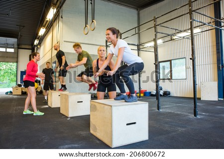 Male and female athletes doing box jumps at gym - stock photo
