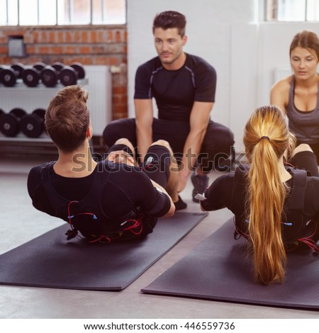 Male and female athletes perform sit ups on yoga mats in fitness studio as their instructors help them