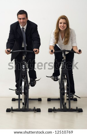 Male and female business colleagues facing forward while riding exercise bikes. Vertically framed - isolated shot. - stock photo