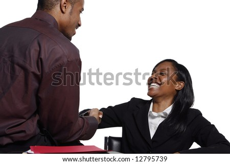 Male and female business colleagues smiling broadly and shaking hands