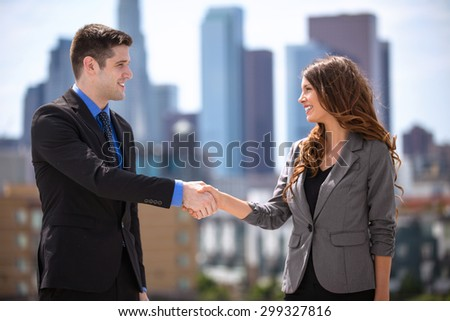 Male and Female business couple group leaders shaking hands downtown city - stock photo