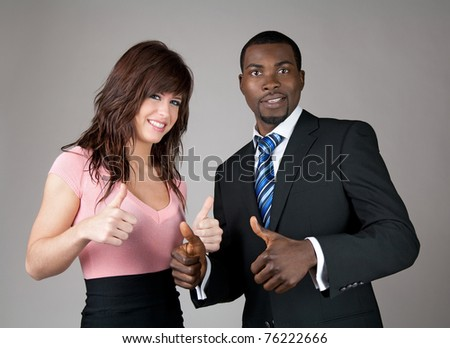 Male and female business partners going thumbs up.