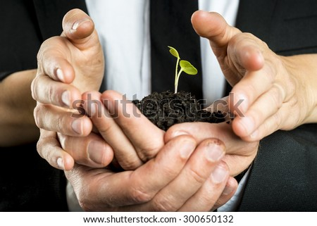 Male and female business partners nurturing a new plant united to protect a green fragile sprout grown in fertile soil, concept of ecology and business start up. - stock photo