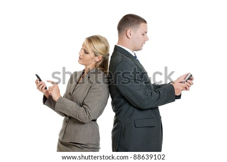Male and female business people back to back looking at their smart phones isolated on a white background