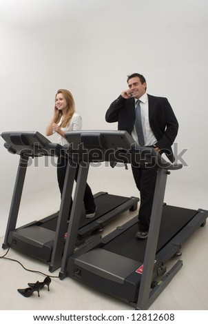 Male and female businesspeople jogging on a treadmill while talking on their phones - stock photo