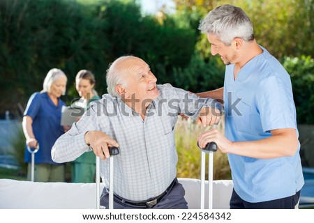 Male and female caretakers helping elderly people in nursing home - stock photo