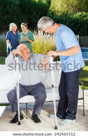Male and female caretakers helping senior people in nursing home - stock photo