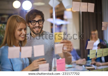 Male and female co-workers reading reminders in office - stock photo
