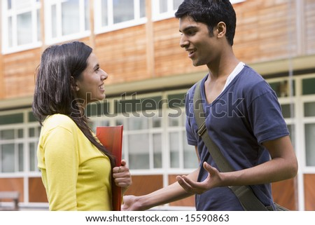 Male and female college students talking on campus - stock photo
