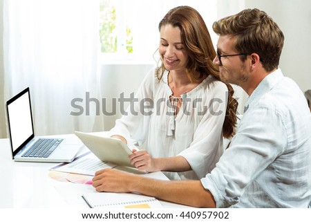 Male and female collegues discussing document at desk in office