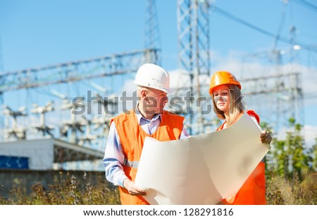 male and female construction workers in the helmet against electrical designs - stock photo