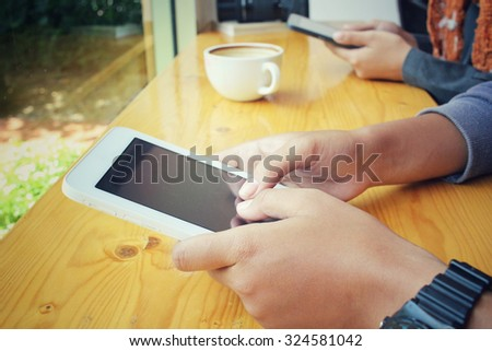 Male and female couple with tablet sitting indoor in trendy urban cafe.