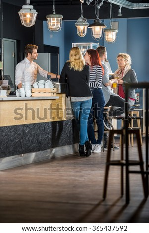 Male and female customers with bartender standing at counter in bar - stock photo