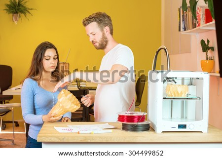 Male and female 3D developers discussing over product at counter in printing studio - stock photo