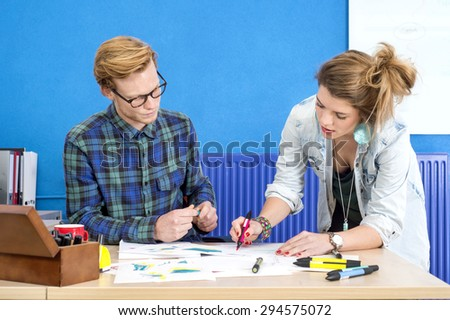 Male and female designers discussing plan at desk in creative office - stock photo