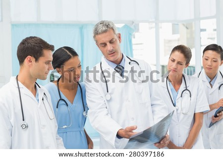 Male and female doctors examining x-ray in the medical office - stock photo