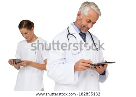 Male and female doctors using digital tablets over white background - stock photo