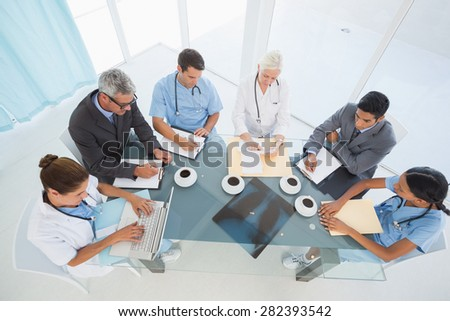 Male and female doctors using laptop in the medical office - stock photo
