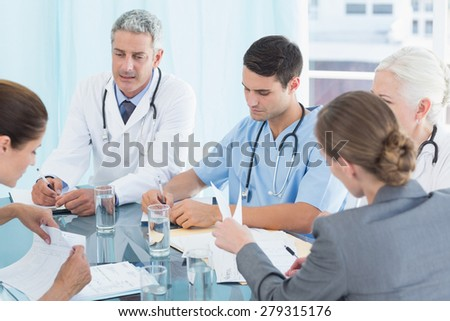 Male and female doctors working on reports in medical office - stock photo