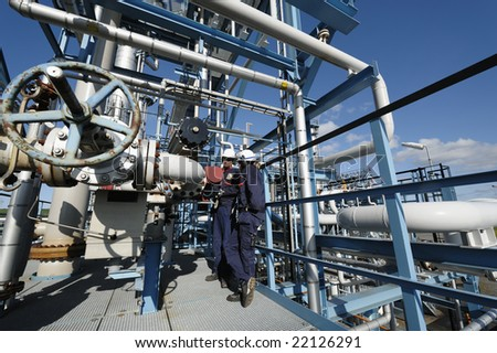 male and female engineer high up on pipelines inside oil industrial complex - stock photo