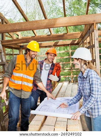 Male and female engineers discussing over blueprint in incomplete wooden cabin at site