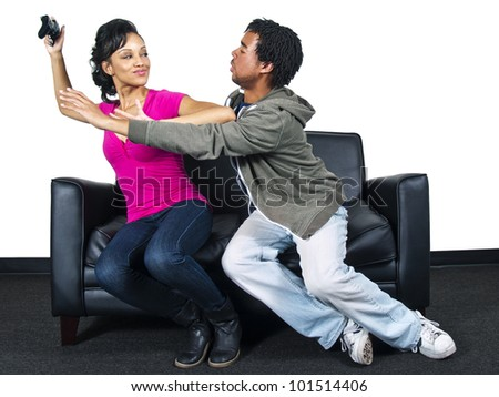male and female fighting over a video game controller - stock photo