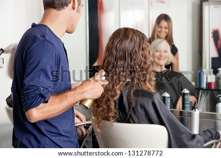 Male and female hairdresser setting up client's hair at beauty salon - stock photo