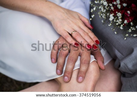 male and female hand with a wedding ring, a female hand with red nails, manicure, love, bouquet of red and white flowers, wedding flowers, wedding rings on hands - stock photo