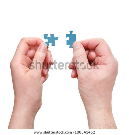 male and female hands connecting little puzzle pieces isolated on white background - stock photo