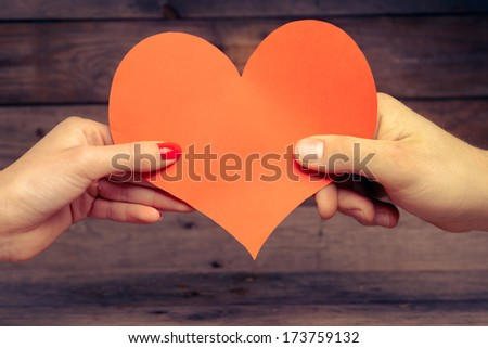 Male and female hands hold red paper heart, concept of love - stock photo