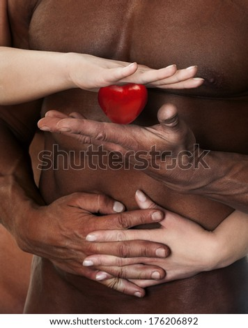 Male and female hands holding red heart against muscular torso. Symbol of safety, love and health - stock photo