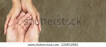 Male and female hands in gentle embrace on parchment banner background - stock photo