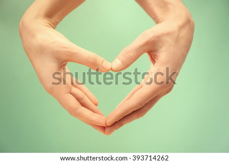 Male and female hands making heart with fingers on turquoise background - stock photo