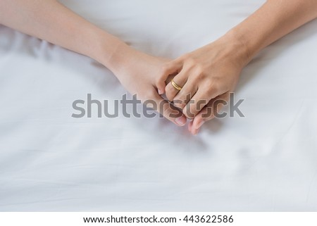 Male and female hands on white fabric background
