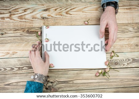 Male and female hands reaching out to touch notepads. Romantic correspondence discussion. Top view. Cool wooden texture background - stock photo