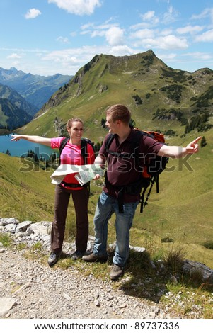 Male and female hikers in the German Alps near Oberstdorf searching the right direction