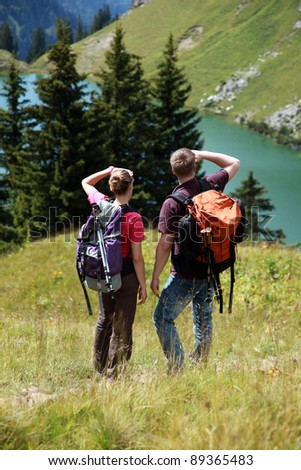 Male and female hikers in the German Alps near Oberstdorf searching the right trail. - stock photo