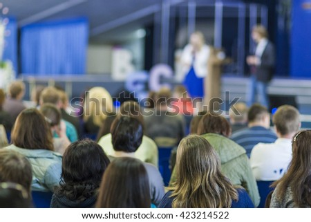 Male and Female Hosts Performing on Stage In front of the Large Group of People. Horizontal Image Composition - stock photo