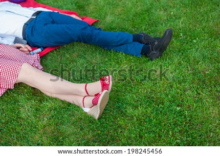 Male and female legs and red shoes - stock photo