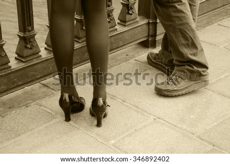 Male and female legs. Closeup. Couple on the bridge over Seine river in Paris. Gender and lifestyle differences concept. Aged photo. Sepia. - stock photo