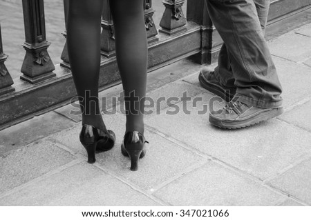 Male and female legs. Closeup. Couple on the bridge over Seine river in Paris. Gender and lifestyle differences concept. Aged photo. Black and white. - stock photo