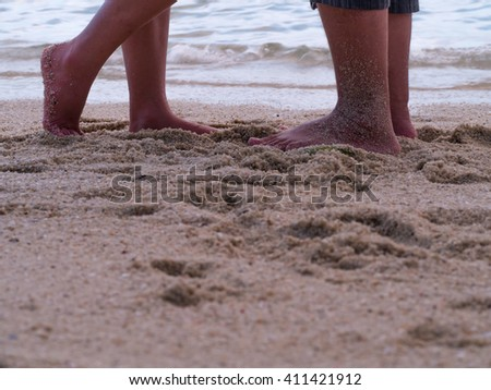 Male and female legs during a date on sandy beach. Close up of love couple feet standing on the beach. Summer in love. - stock photo