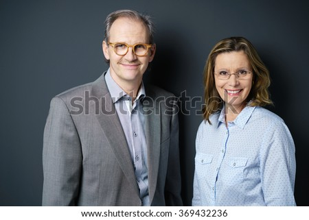 male and female manager standing against grey background in the studio