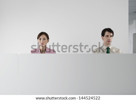 Male and female office workers behind the cubicle wall at office - stock photo