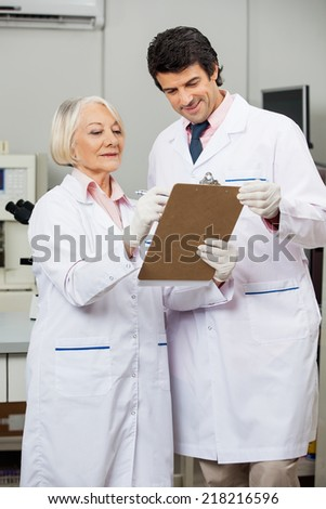 Male and female researchers writing on clipboard in medical laboratory