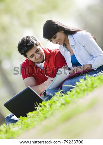 Male and female students outdoors studying together. - stock photo