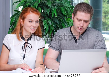 Male and female students studying using laptop - stock photo