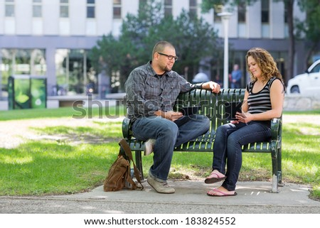 Male and female students with digital tablets sitting on bench at university campus - stock photo