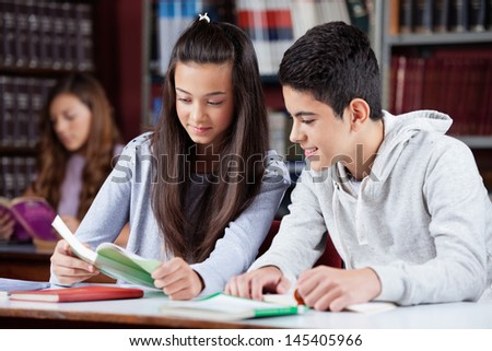 Male and female teenage friends studying together at desk in library