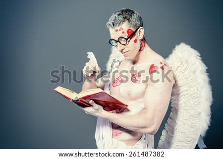Male angel Cupid with a bow and arrows of love holds opened book. Valentine's day. Love concept. - stock photo
